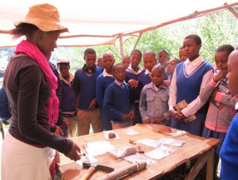 'M'e Matikoe Matsoso demonstrates how stone tools work to students from Metolong